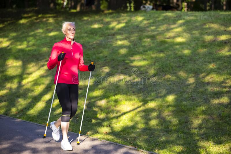 Full Length Portrait of Positive Sportive Senior Woman Doing Nordic Walking in Park. Horizontal image Orientation. Full Length Portrait of Positive Sportive stock photography