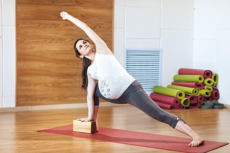 Full length portrait of young pregnant fitness model in sportswear doing yoga, pilates training, lunge exercise, Utthita Parsvakon stock image