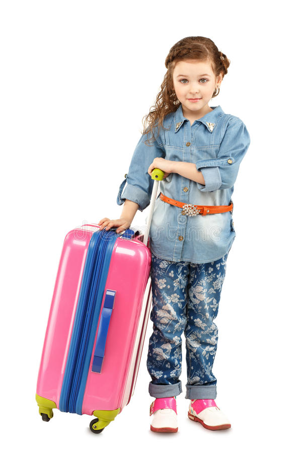 Full-length portrait of a pretty little girl with big pink suitcase on wheels. Isolated on white background. Concept holidays and vacations stock image
