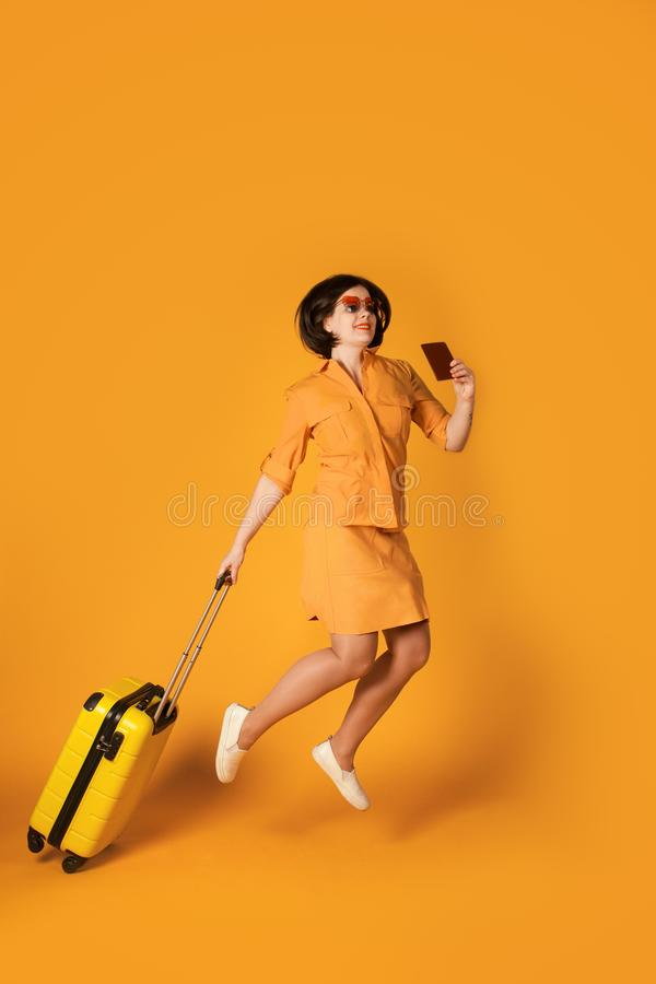 Full length portrait of pretty woman jumping with yellow suitcase. Happy girl traveler having fun stock photos