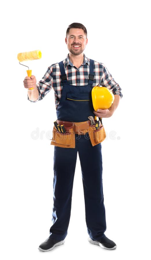 Full length portrait of professional construction worker with hard hat, paint roller and tool belt. On white background royalty free stock photography