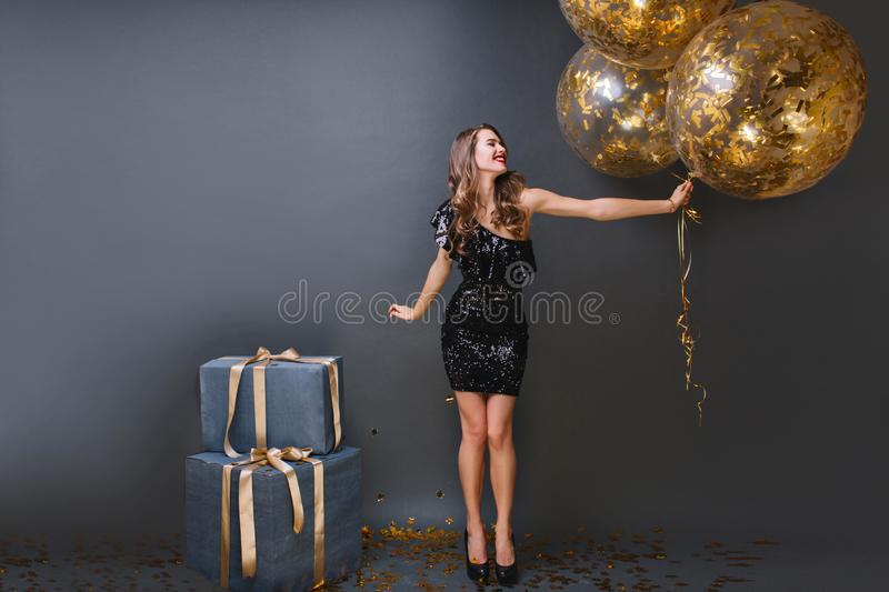 Full-length portrait of refined european girl wears black dress at birthday party. Blissful long-haired lady with royalty free stock photo