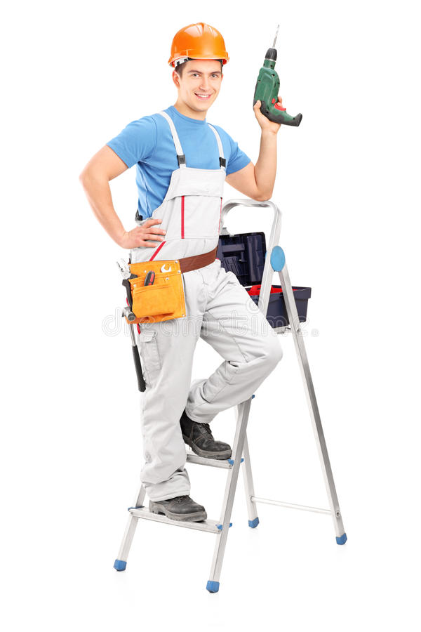 Full length portrait of a repairman with a hand drilling machine. Standing on a ladder on white background stock photography
