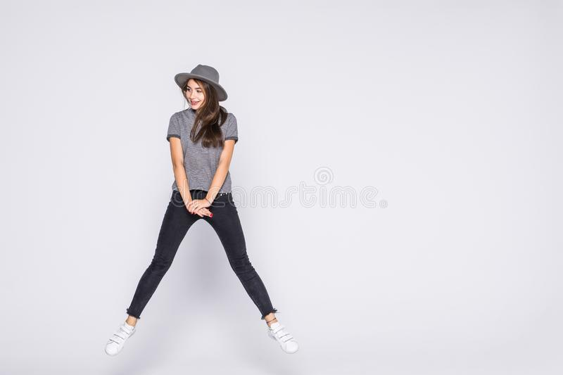 Full length portrait of satisfied american woman wearing jeans and t-shirt jumping isolated over white background. Full length portrait of satisfied american royalty free stock image