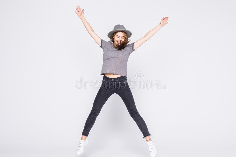 Full length portrait of satisfied american woman wearing jeans and t-shirt jumping isolated over white background. Full length portrait of satisfied american stock photos