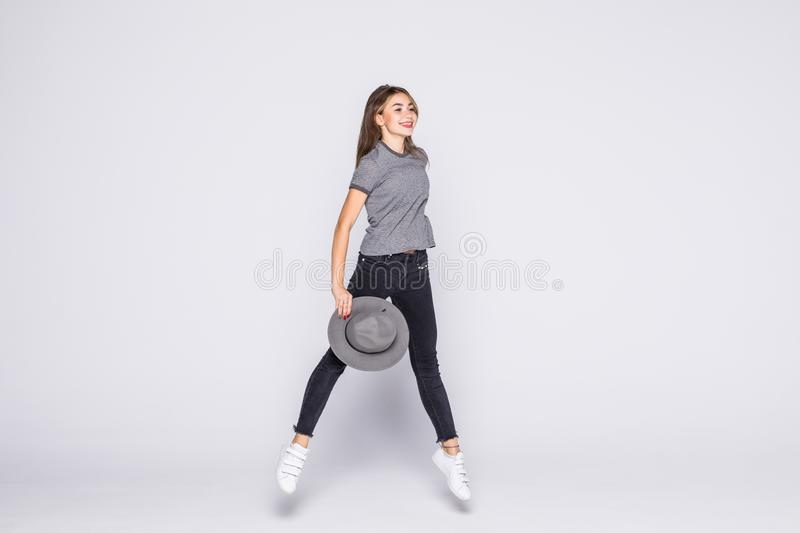 Full length portrait of satisfied american woman wearing jeans and t-shirt jumping isolated over white background. Full length portrait of satisfied american stock image