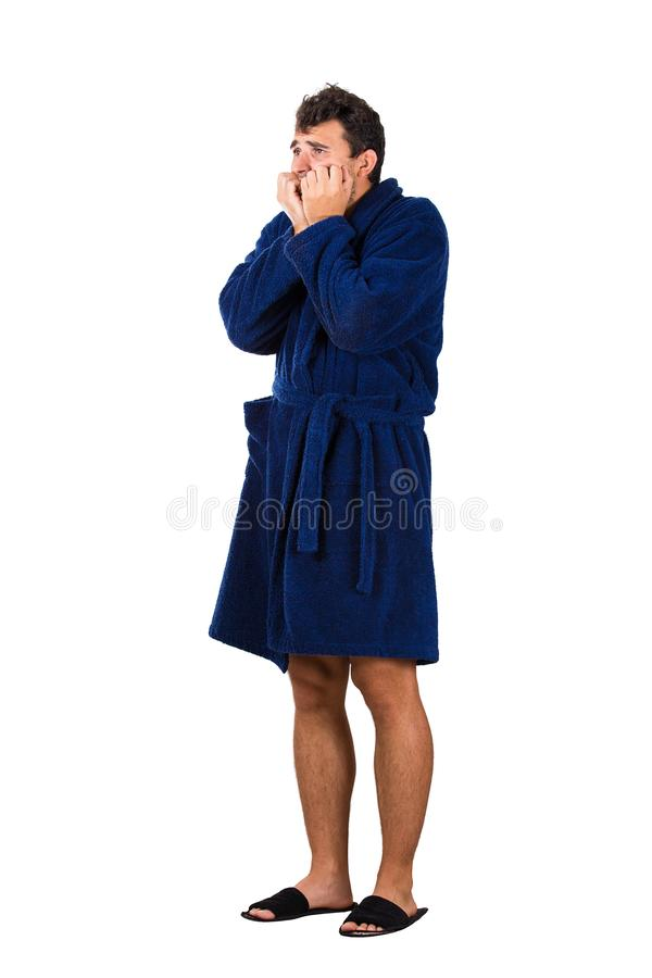 Full length portrait of scared and worried young man messy hair, wears blue bathrobe, waking up after dreamt a nightmare, bites royalty free stock photo
