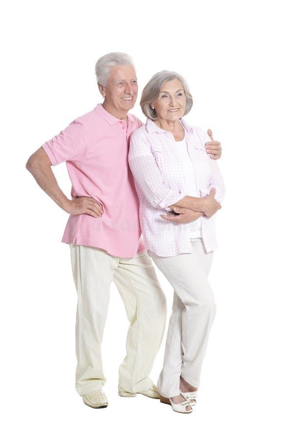 Full length portrait of senior couple embracing on white background. Full length portrait of senior couple embracing isolated on white background stock image