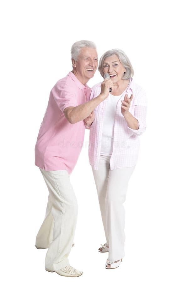 Full length portrait of senior couple singing isolated. On white background royalty free stock photography