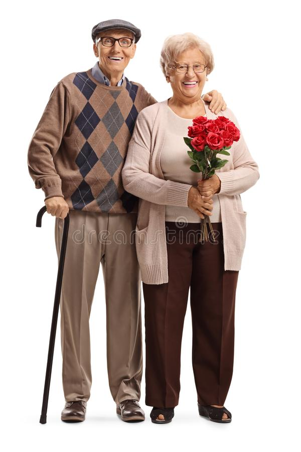 Senior couple standing with red roses. Full length portrait of a senior couple standing with red roses isolated on white background royalty free stock photos
