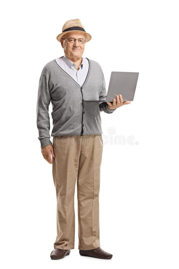 Senior gentleman standing with a laptop stock image