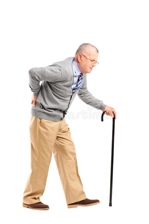 Full length portrait of a senior gentleman walking with cane and. Suffering from back pain isolated on white background royalty free stock photos