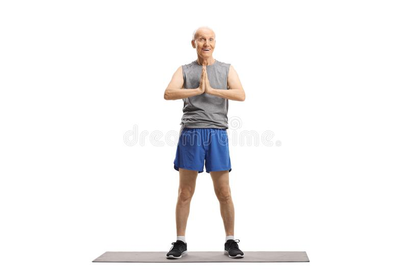 Senior man practicing yoga. Full length portrait of a senior man practicing yoga isolated on white background stock photography
