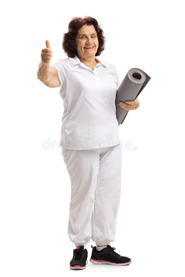 Senior woman with an exercise mat showing thumbs up stock images