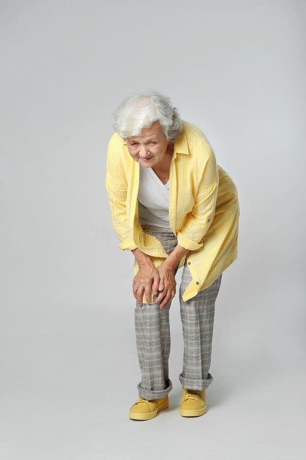 Full length portrait of senior woman having knee problems stock images