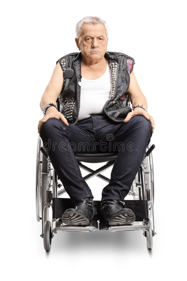 Serious mature male punker in a wheelchair stock images