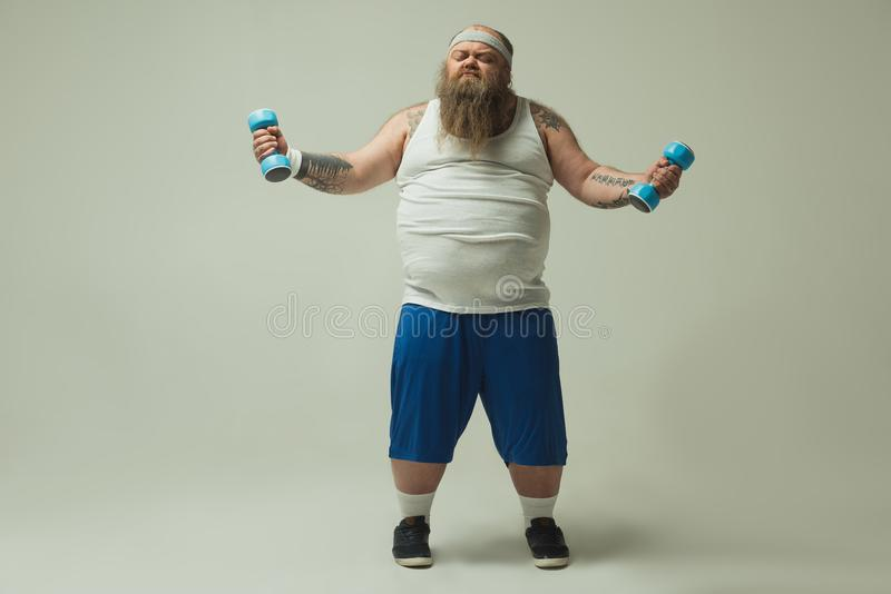 Obese man doing exercise with heavy weights stock photography