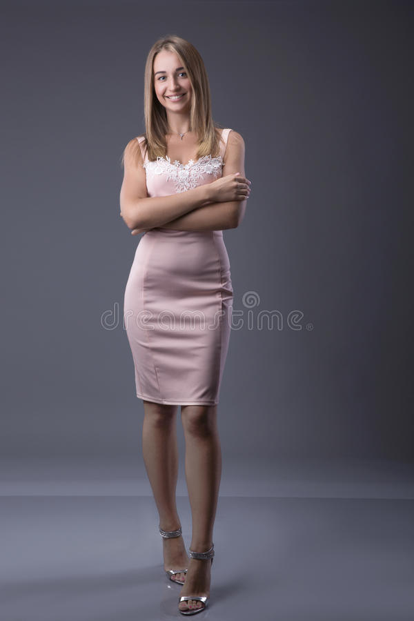 Full Length Portrait of a Blonde Woman in Fashion Dress with Hands on Hips. Gray Background. Body Language Concept. Toned Ins stock images