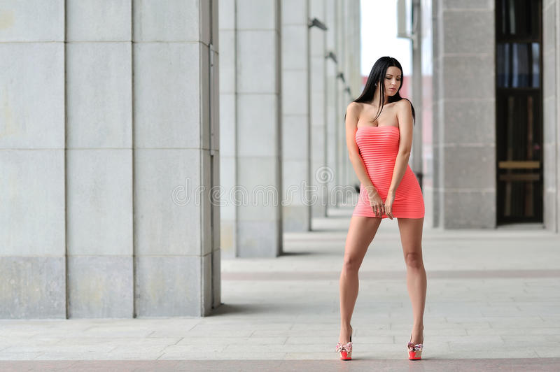 Full length portrait of a brunette woman in little pink fas stock photography