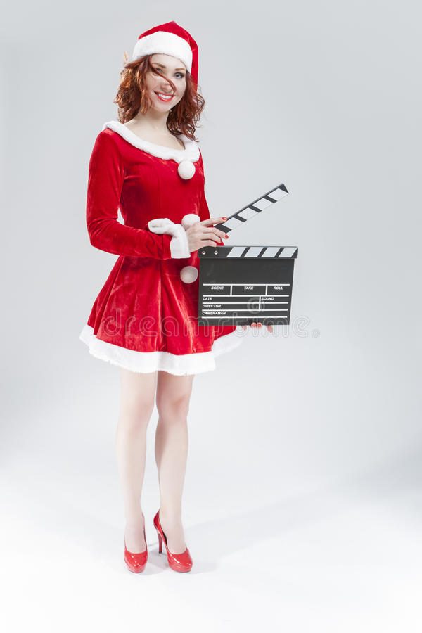 Full Length Portrait Of female Santa Girl with Clapperboard. Posing Against White Background.Vertical Shot stock photography
