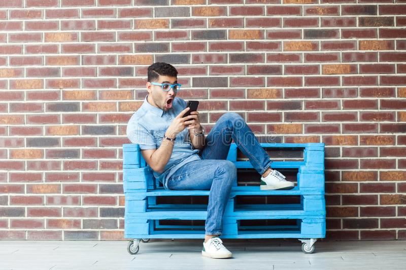 Full length portrait of shocked young bearded man in casual style and eyeglasses sitting on blue wooden pallet, holding smartphone. And reading unbelievable stock images