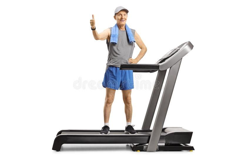 Senior man standing on a treadmill and showing thumbs up stock images