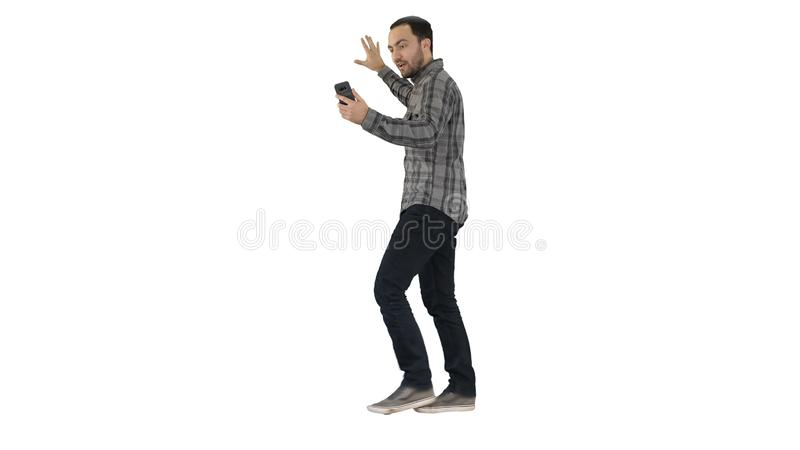Handsome bearded man recording vlog blog with smartphone while walking on white background. stock photo