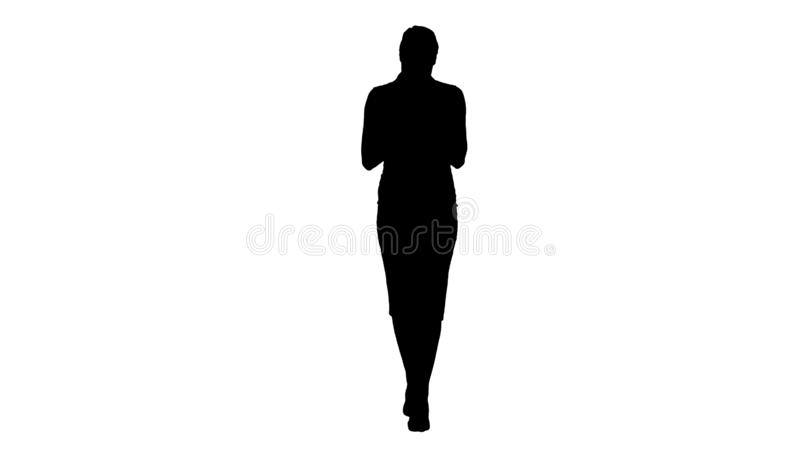 Silhouette Successful female employer typing text message on her cellphone while walking. stock illustration