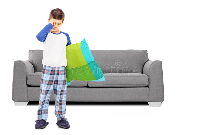 Full length portrait of sleepy boy in pajamas standing in front. Of sofa isolated on white background stock photos