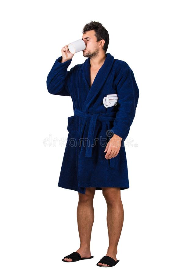 Full length portrait of sleepy young man messy hair, wears blue bathrobe, drinking coffee from his cup as holding a morning stock photography