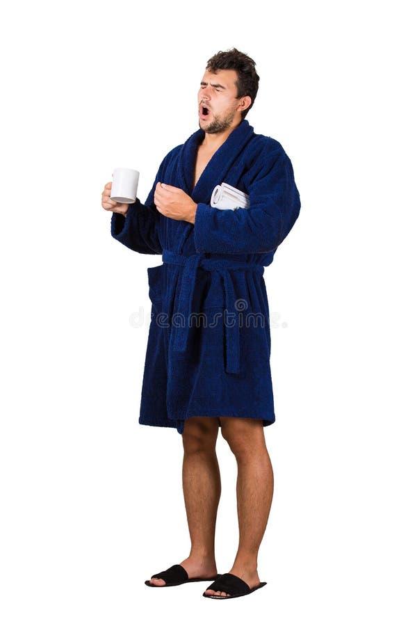 Full length portrait of sleepy young man messy hair, wears blue bathrobe, eyes closed yawning as holding a tea mug and newspaper stock photo