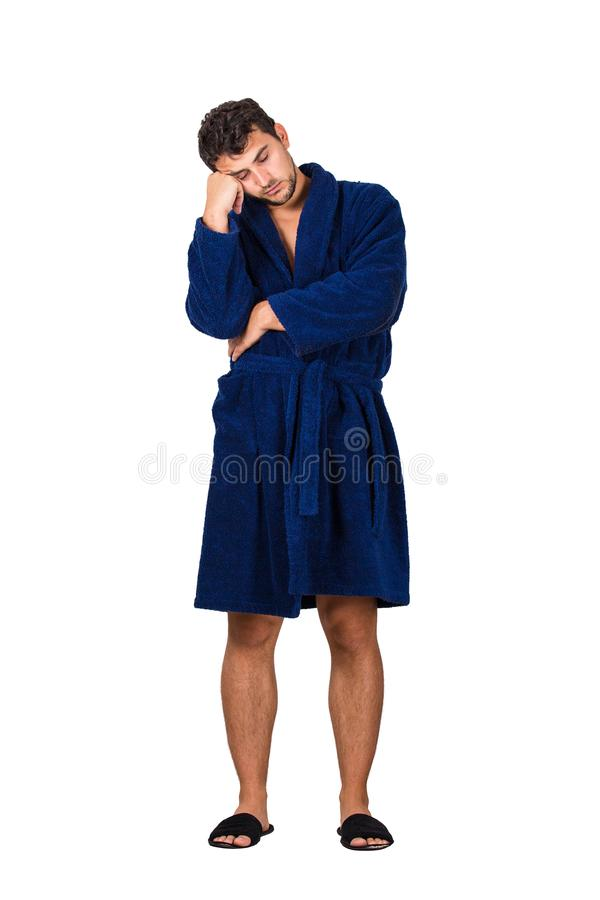 Full length portrait of sleepy young man wears blue bathrobe holding hand to forehead, eyes closed feel tired needs to sleep stock images