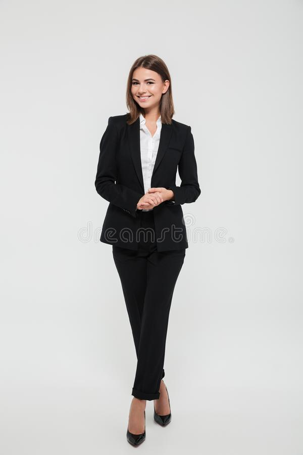 Full length portrait of smiling attractive businesswoman in suit. Posing while standing with arms crossed and looking at camera isolated over white background royalty free stock photography