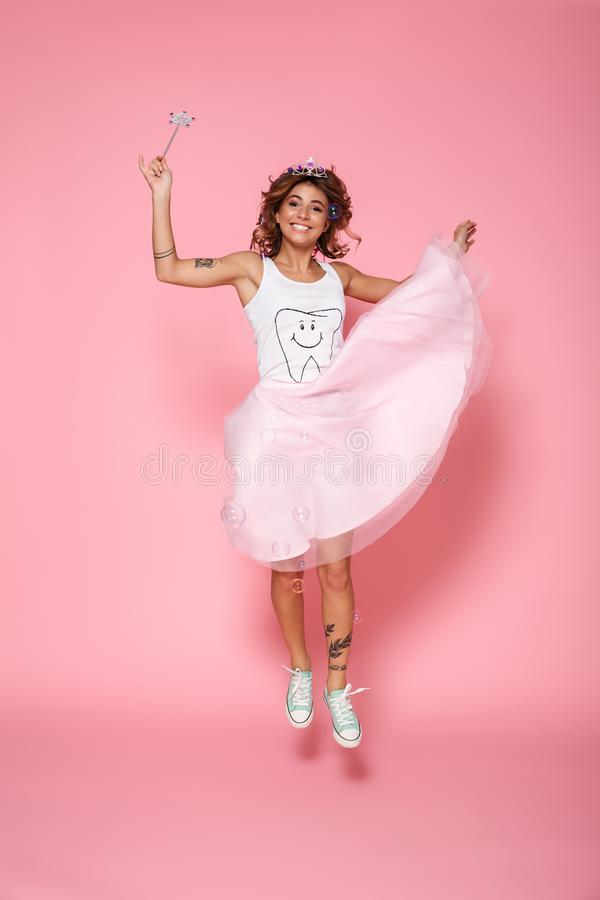 Full length portrait of smiling attractive girl dressed like princess holding magic wand, jumping and looking at camera royalty free stock images