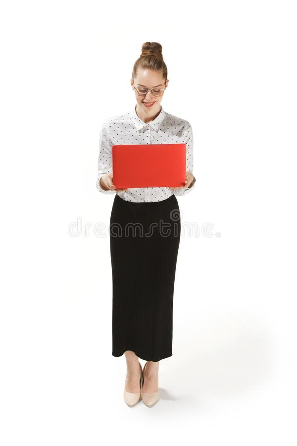 Full length portrait of a smiling female teacher holding a laptop isolated against white background royalty free stock image