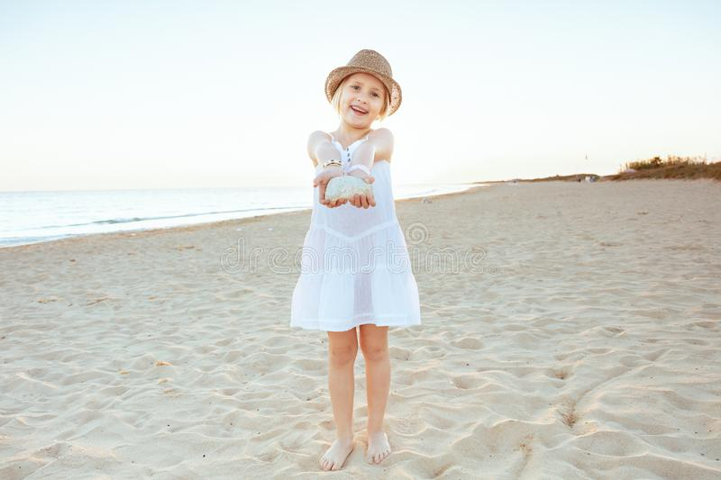 Tourist girl on ocean shore in evening showing amazing find. Full length portrait of smiling fit tourist girl in white dress and hat on the ocean shore in the royalty free stock images