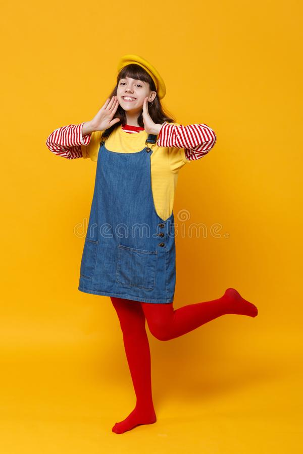 Full length portrait of smiling girl teenager in french beret and denim sundress keeping hands near face isolated on stock image