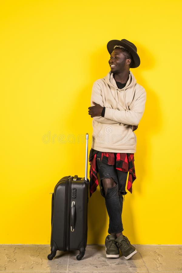 Full length portrait of a smiling happy afro american man in summer clothes holding suitcase and looking at camera isolated over royalty free stock photography