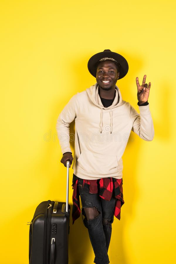 Full length portrait of a smiling happy afro american man in summer clothes holding suitcase and looking at camera isolated over royalty free stock image