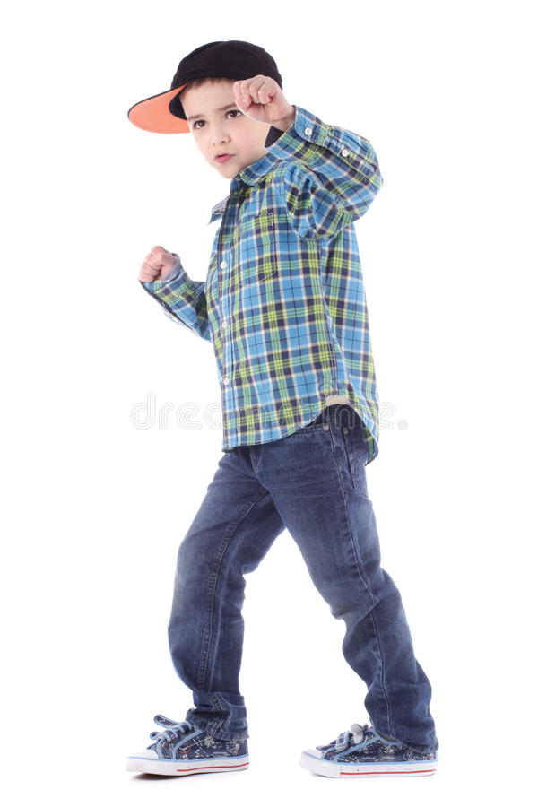 Full length portrait of smiling little boy in jeans and cup royalty free stock photos