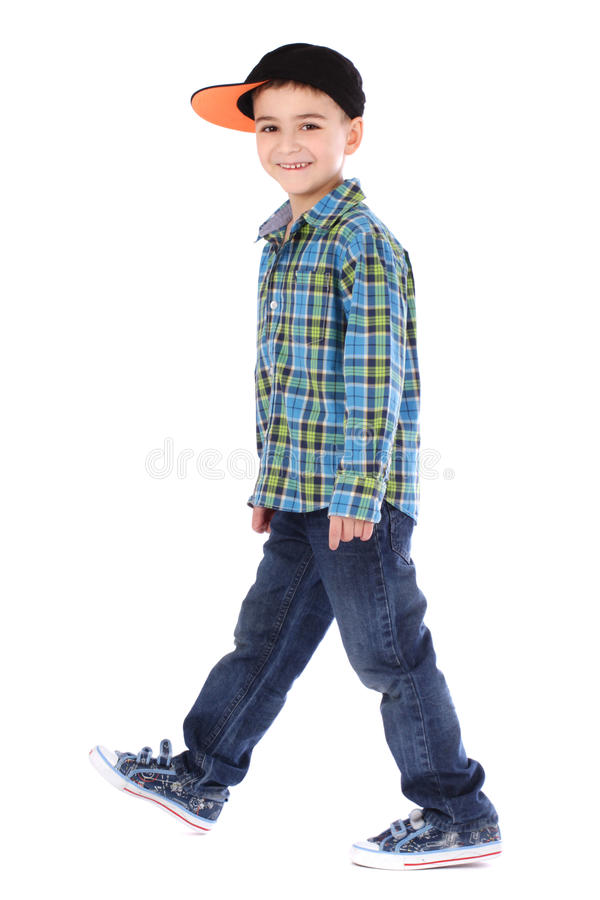 Full length portrait of smiling little boy in jeans and cup royalty free stock image