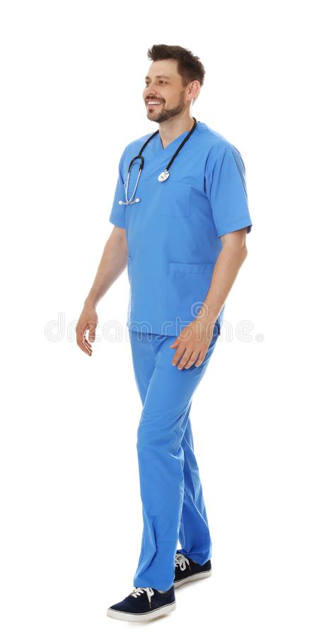 Full length portrait of smiling male doctor in scrubs isolated. Medical staff. Full length portrait of smiling male doctor in scrubs isolated on white. Medical stock photography