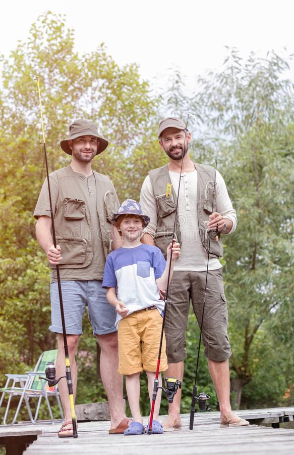 Full length portrait of smiling males standing with fishing rods on pier against trees. Portrait of smiling males standing with fishing rods on pier against royalty free stock photo