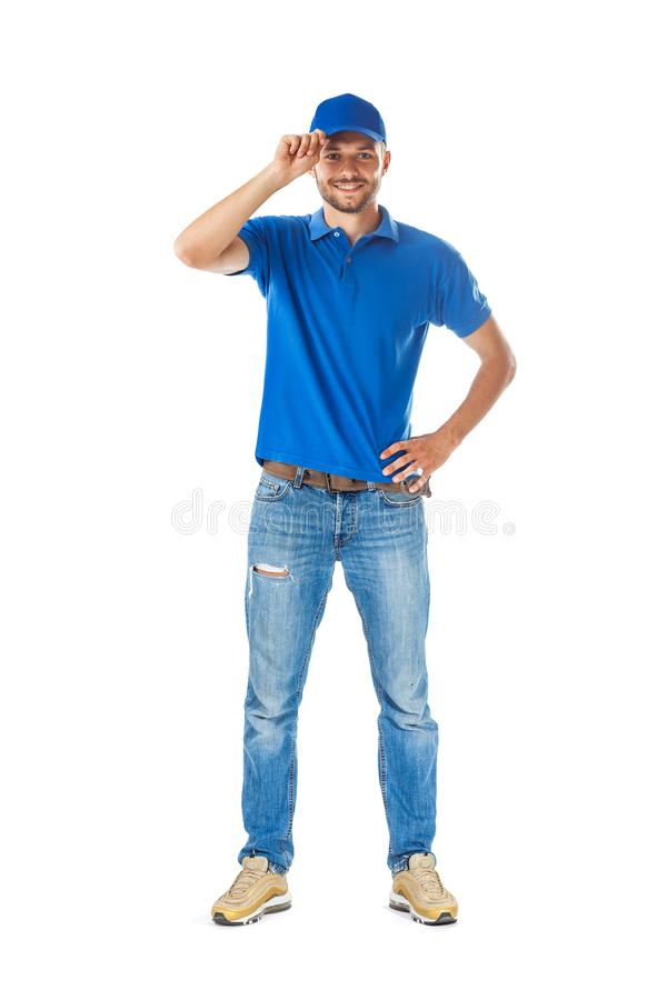 Full length portrait of smiling man in in blue uniform touching. His cap in greeting isolated on white backgroundhandsome man in blue uniform royalty free stock photos