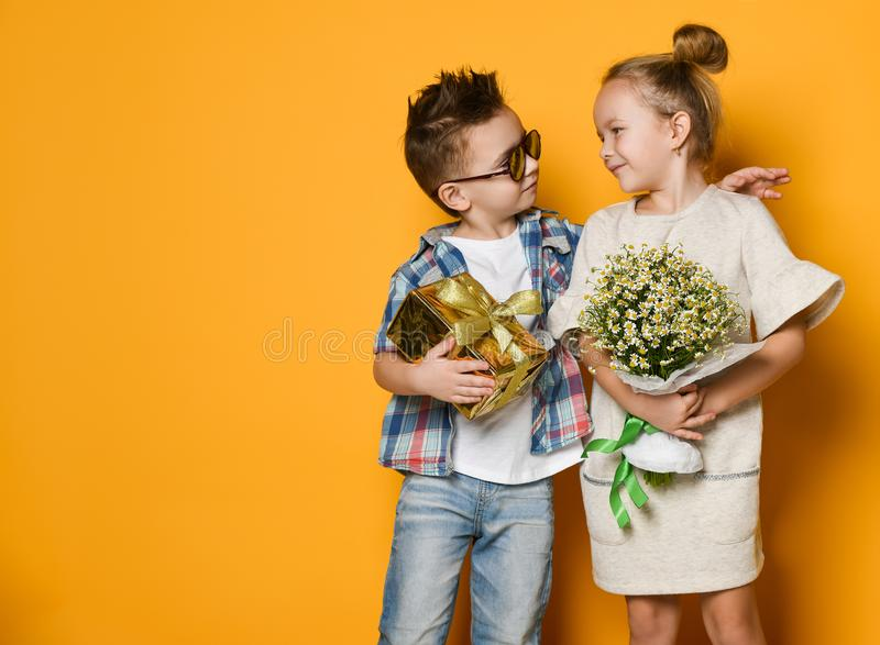 Full length portrait of a smiling man giving a present box to his girlfriend over gray wall stock photo