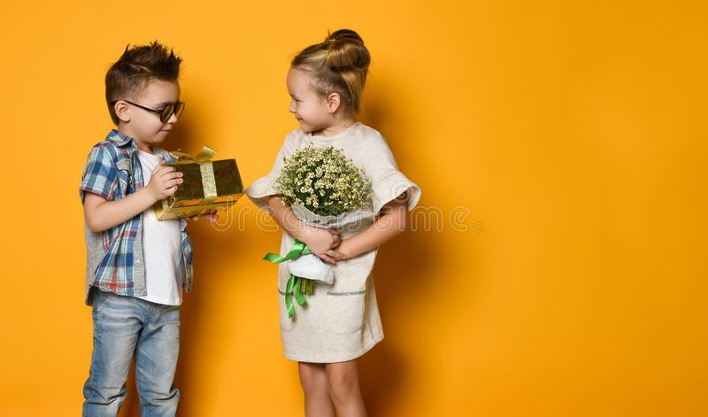 Full length portrait of a smiling man giving a present box to his girlfriend over gray wall royalty free stock image
