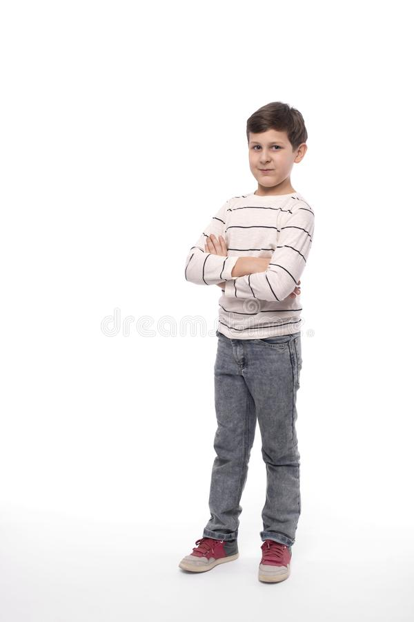 Full-length portrait of a smiling teenager boy  with arms crossed against white background in studio royalty free stock photography