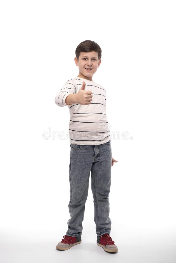 Full-length portrait of a smiling teenager boy civing you an approving gesture,  stock photo