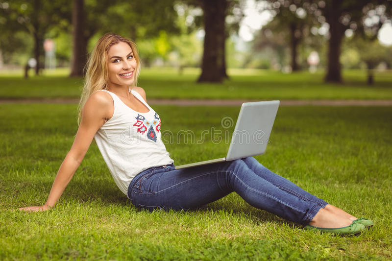 Full length portrait of smiling woman holding laptop at park stock photo