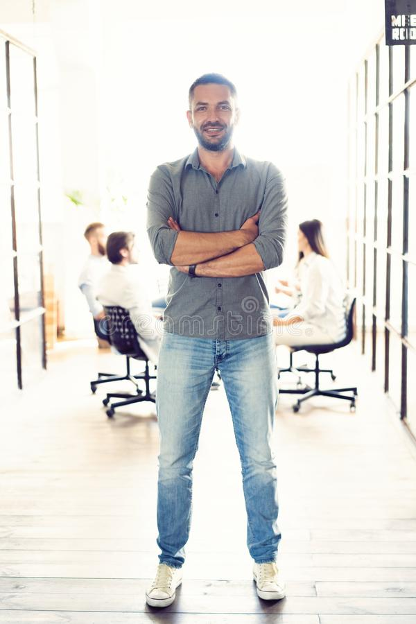 Full length portrait of smiling young man standing in doorway of office. Creative male executive at startup with people royalty free stock photography